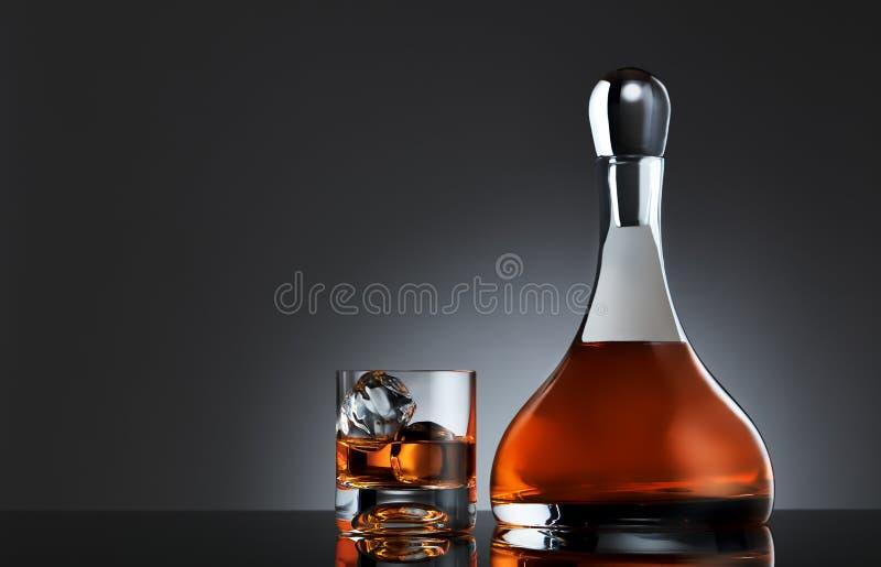 充分杯与冰的威士忌酒和一个圆的玻璃水瓶唯一麦芽威士忌 免版税库存照片