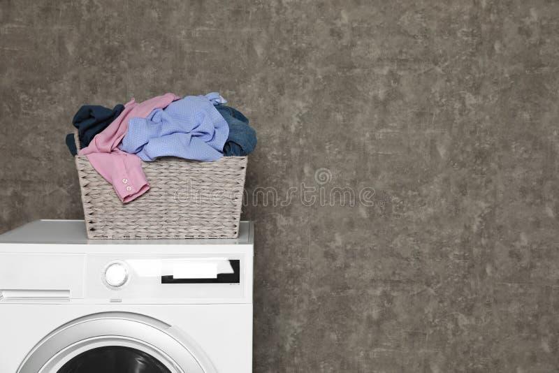 充分柳条洗衣篮在洗衣机的肮脏的衣裳在颜色墙壁附近 免版税图库摄影