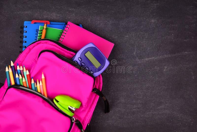 充分桃红色背包反对黑板背景的学校用品,顶视图 图库摄影
