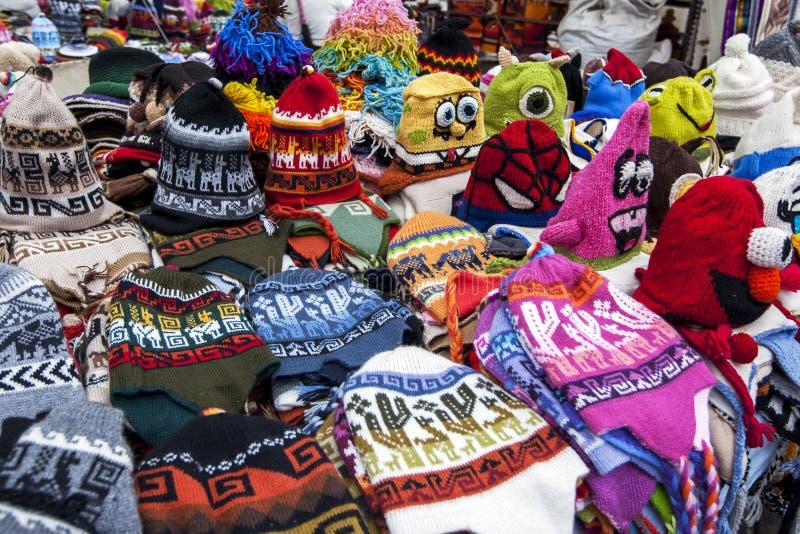 充分桌五颜六色的童帽待售在Otavolo印地安市场上在厄瓜多尔 图库摄影