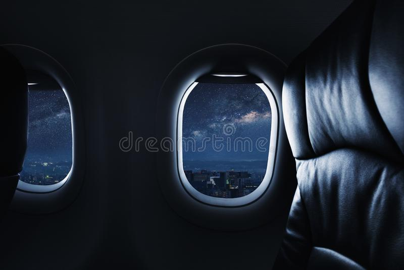 充分注视着通过飞机窗口与天空的夜星和银河 库存照片