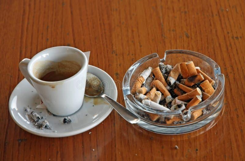 充分烟灰缸烟头和一个杯子浓咖啡 免版税图库摄影