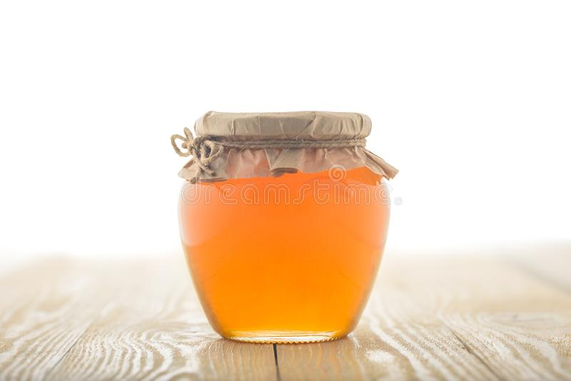 充分玻璃瓶子对此的蜂蜜在木背景 免版税库存图片