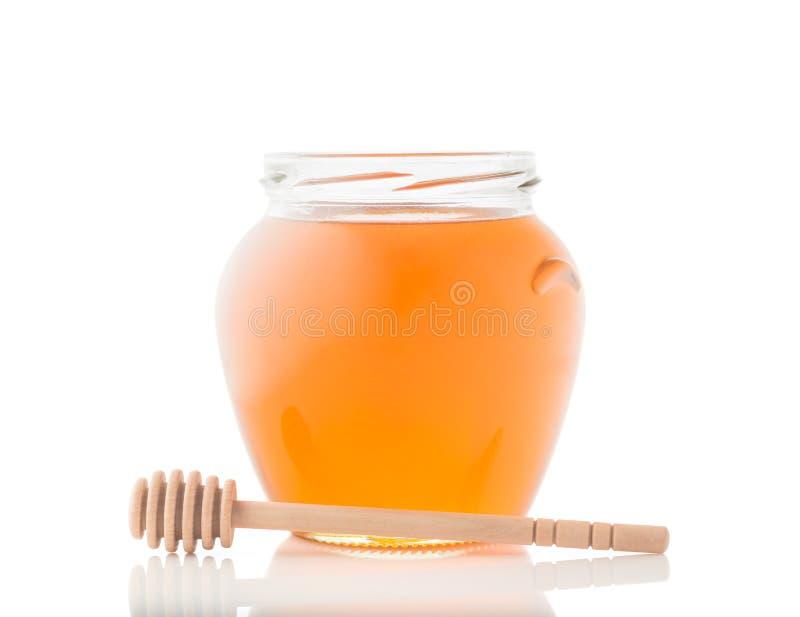 充分玻璃瓶子蜂蜜和木棍子对此在白色背景 库存图片