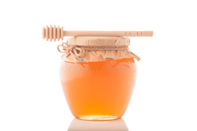 充分玻璃瓶子蜂蜜和木棍子对此在白色背景 免版税库存图片