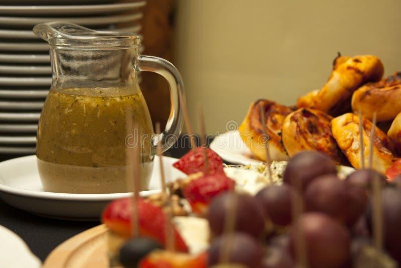 充分的容器醋调味汁、承办酒席、食品供应特写镜头、宏指令、板材有很多新鲜的鲜美食物和开胃菜 免版税库存图片