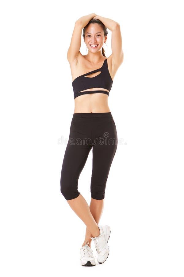 充分的摆在运动的成套装备的身体美丽的年轻亚裔妇女反对被隔绝的白色背景 免版税图库摄影