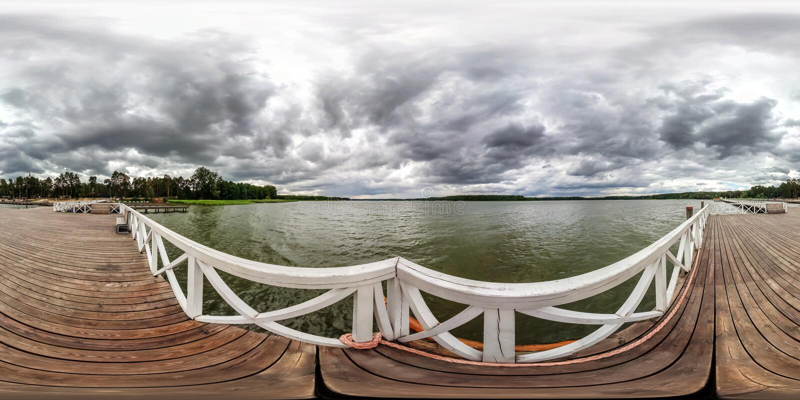 充分的无缝的球状hdri全景360度在木码头的角度图在巨大的湖的船的灰色雨天空的 免版税库存图片