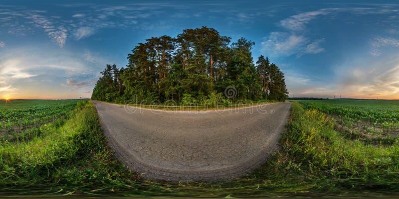 充分的无缝的球状hdri全景360度在石渣路的角度图在夏天晚上日落的领域中与令人敬畏 免版税库存照片