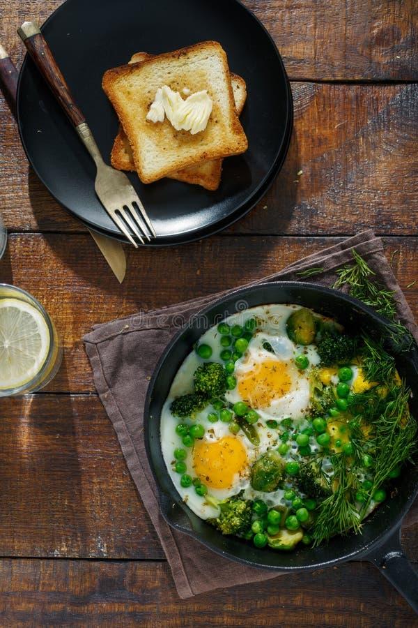充分的早餐桌 与菜的煎蛋在煎锅 免版税库存图片