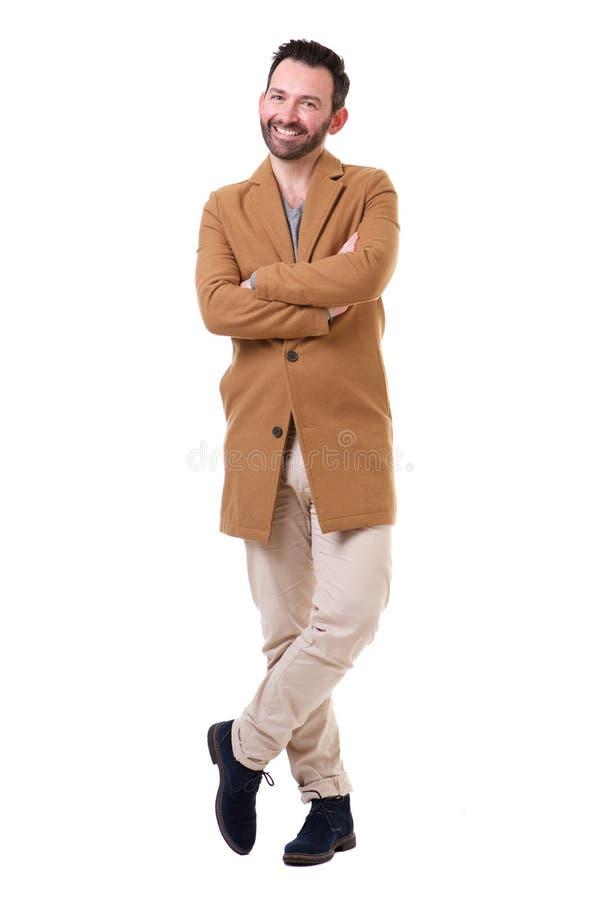 充分的有站立反对白色背景的外套的身体愉快的人 免版税库存照片