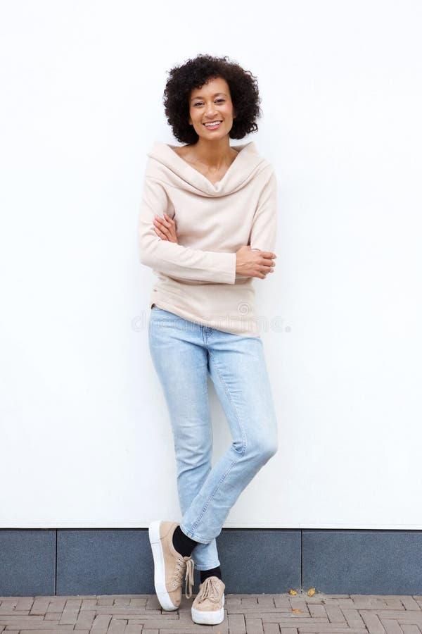 充分的有胳膊的身体微笑的非裔美国人的妇女横渡对白色墙壁 库存照片