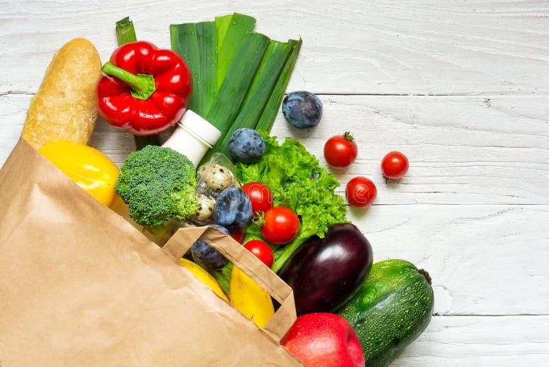 充分的纸袋在白色木背景的另外健康食品 图库摄影