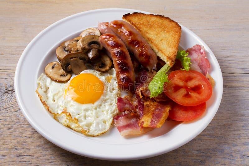 充分的英国或爱尔兰早餐:香肠、烟肉、鸡蛋、蘑菇、蕃茄和多士 免版税库存照片