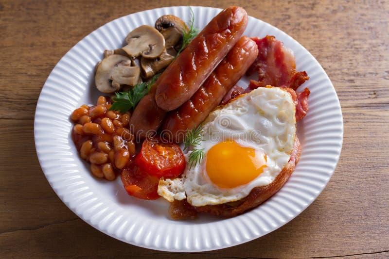充分的英国或爱尔兰早餐:香肠、烟肉、鸡蛋、蘑菇、蕃茄和豆 库存图片
