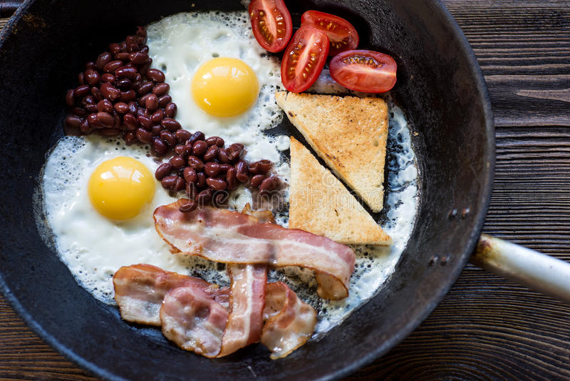 充分的英语烹调了早餐用烟肉、煎蛋和多士 库存图片