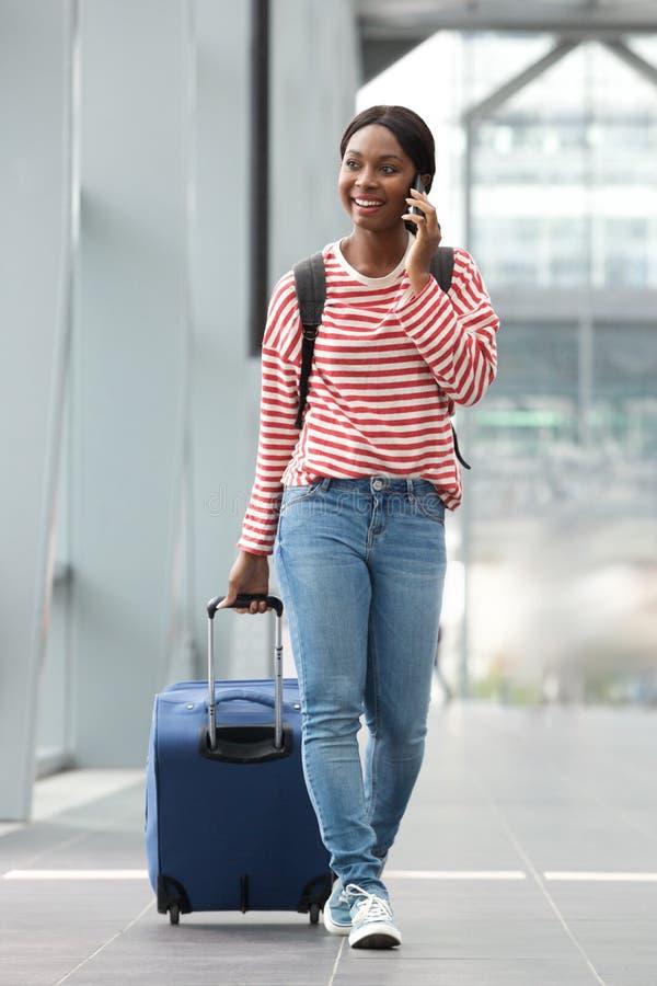 充分的走带着手提箱的身体愉快的年轻黑人妇女在有手机的机场终端 免版税库存照片