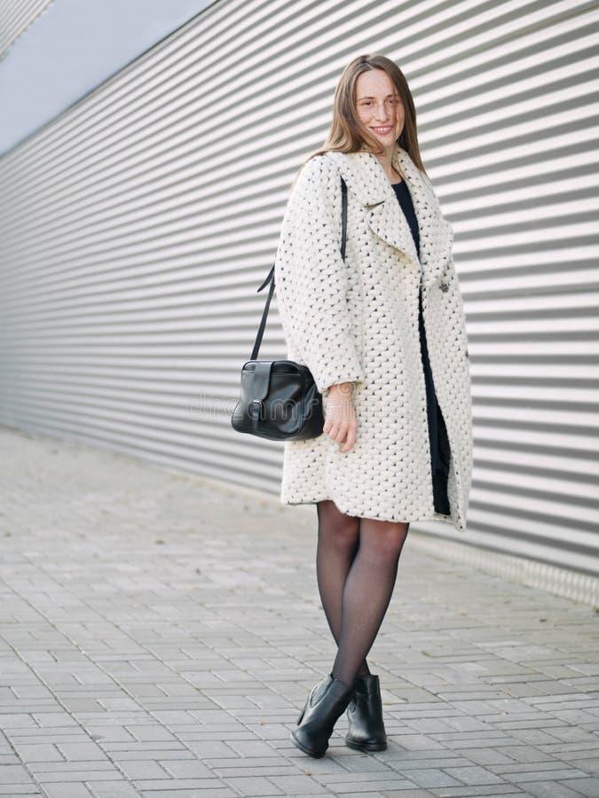 充分的身体射击年轻时髦穿戴的严肃白种人妇女摆在室外在都市城市被弄脏的几何背景寒冷 免版税图库摄影