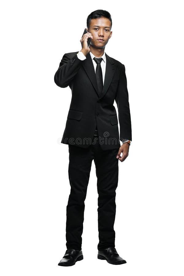 充分的身体年轻亚洲商人叫与智能手机 免版税库存图片
