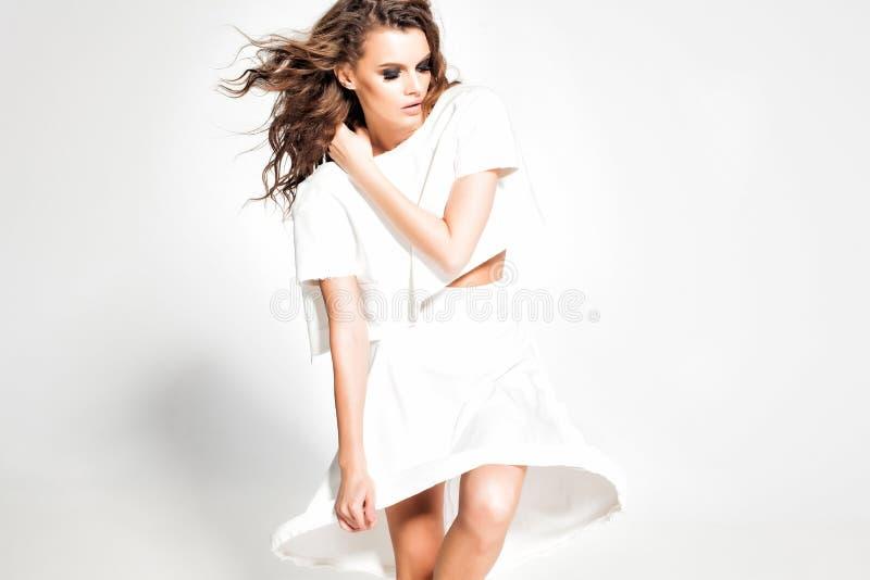 充分的身体美丽的妇女式样摆在白色礼服在演播室 免版税库存图片