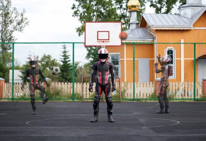 充分的齿轮和盔甲的摩托车骑士踢足球 他投掷在篮子的篮球 库存照片