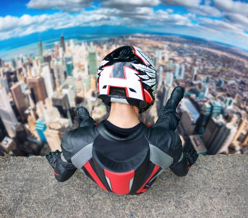 充分的齿轮的摩托车骑士和盔甲坐一个高楼 人在城市看下来 库存图片