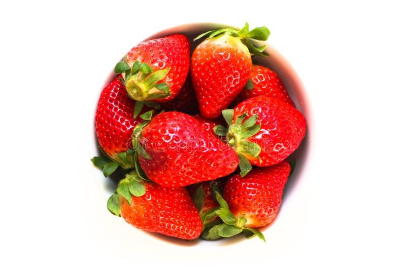 充分碗与在无缝的白色背景隔绝的绿色叶子的新鲜和自然红色草莓 免版税库存照片