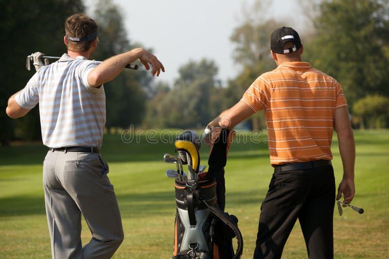 充分站立在高尔夫球场的年轻人在高尔夫球袋棍子旁边 免版税库存图片