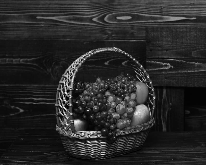 充分篮子在葡萄酒木背景的本地出产的秋天果子 免版税库存图片