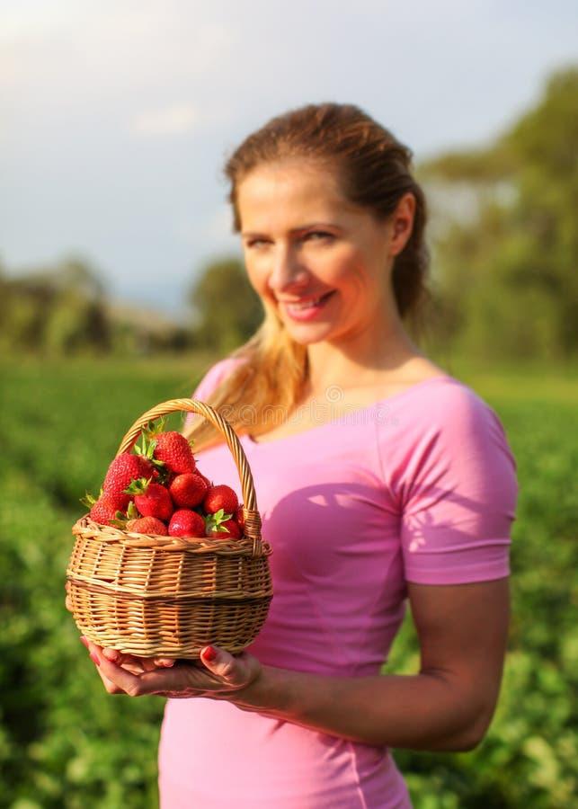 充分篮子红色成熟草莓,被弄脏的少妇holdin 免版税库存图片