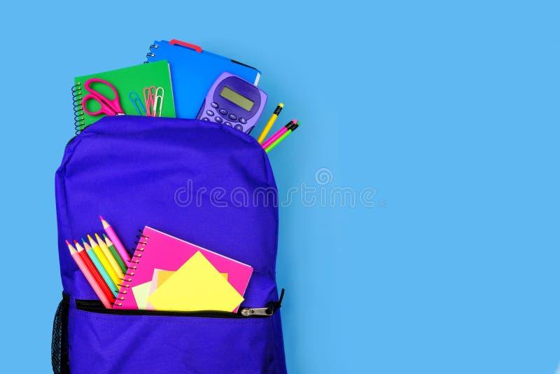 充分紫色背包反对蓝色背景的学校用品,与拷贝空间的顶视图 免版税库存图片