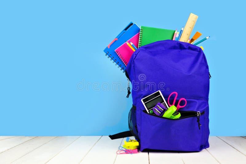 充分紫色背包反对蓝色背景的学校用品 r 库存照片