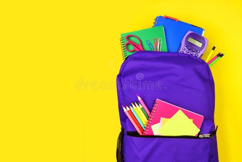 充分紫色背包反对黄色背景的学校用品,与拷贝空间的顶视图 图库摄影