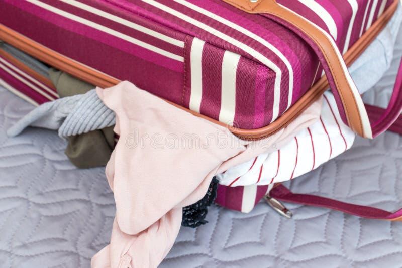 充分红色和白色五颜六色的镶边行李袋子衣裳-旅行和冒险概念 图库摄影