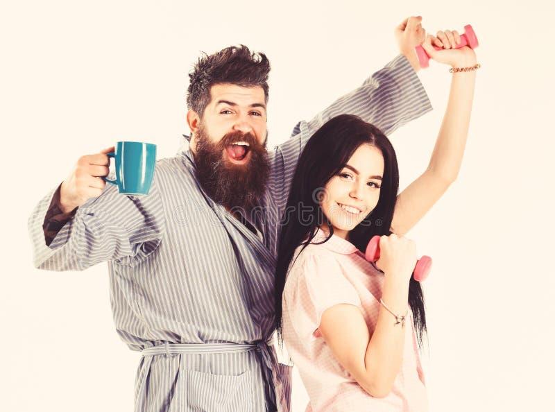 充分结合能量在早晨运动和咖啡以后 愉快的夫妇身分和举行咖啡和哑铃 库存图片