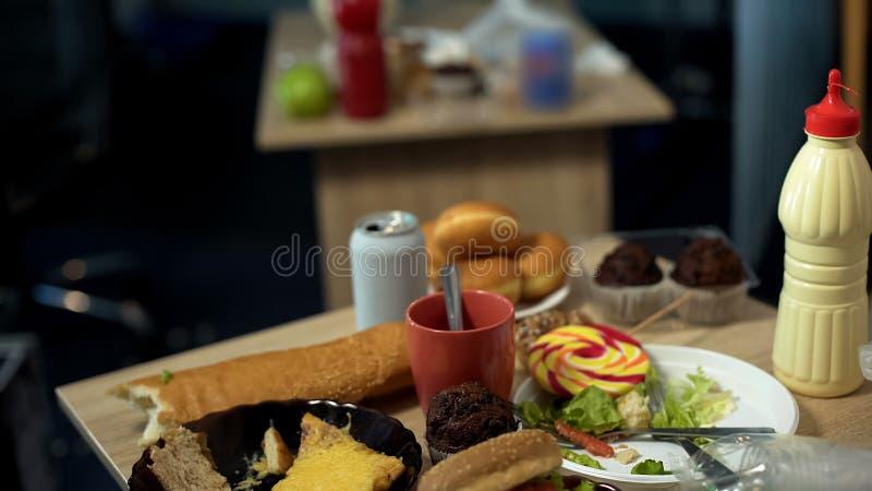 充分肮脏的板材站立在杂乱桌混乱的油腻速食残羹剩饭 库存照片