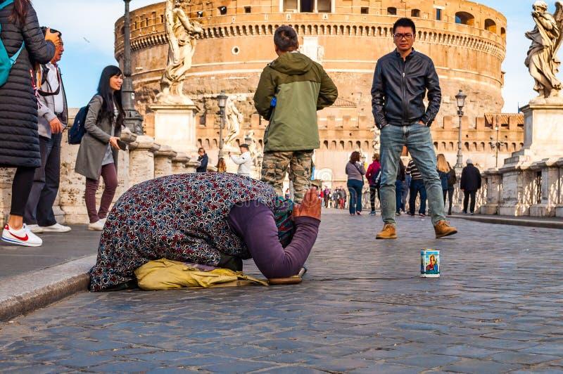 充分要求叫化子的妇女在她的膝盖的施舍在蓬特桑特'安吉洛,哈德良桥梁有圣天使城堡的走的人, 免版税库存照片