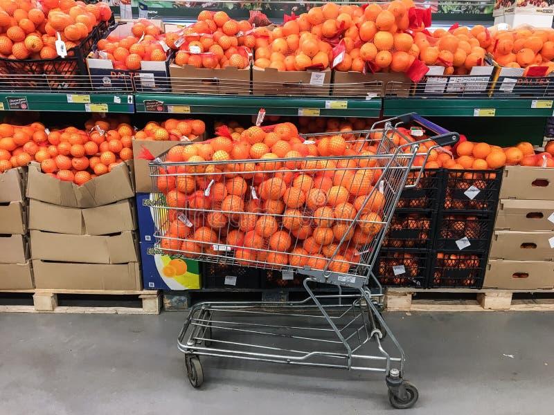 充分超级市场推车和架子桔子 免版税库存照片