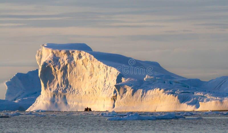 充分黄道带游人被观看反对一座大冰山用白夜的光,南极洲 免版税库存图片