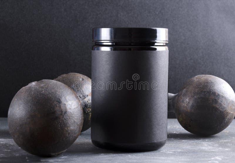 充分黑塑料罐头体育营养,钢钢哑铃 免版税库存照片