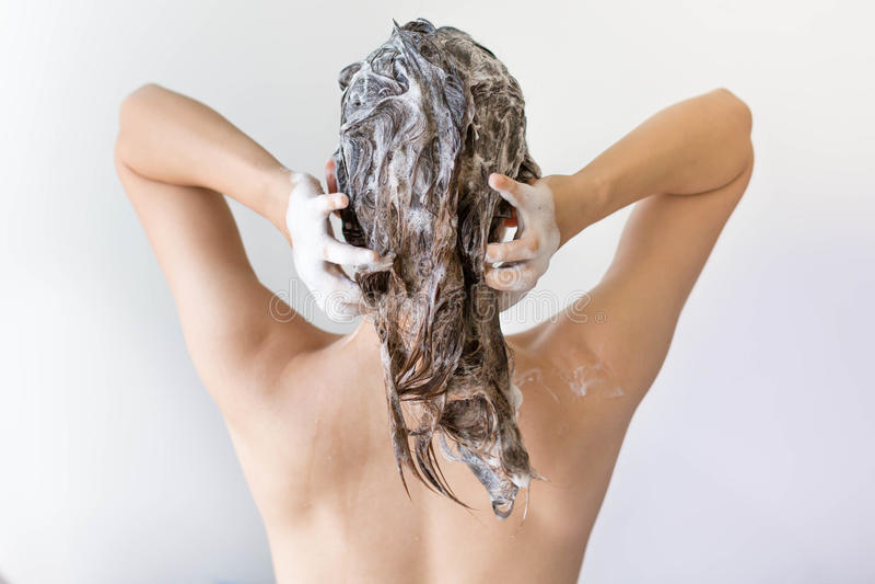 充分洗她的头发在白色背景前面的suds的妇女的后面 图库摄影