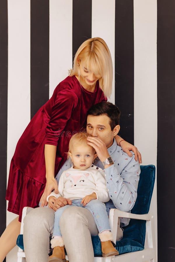 充满一个小女儿、简单的背景、幸福和喜悦的美丽的家庭 库存照片