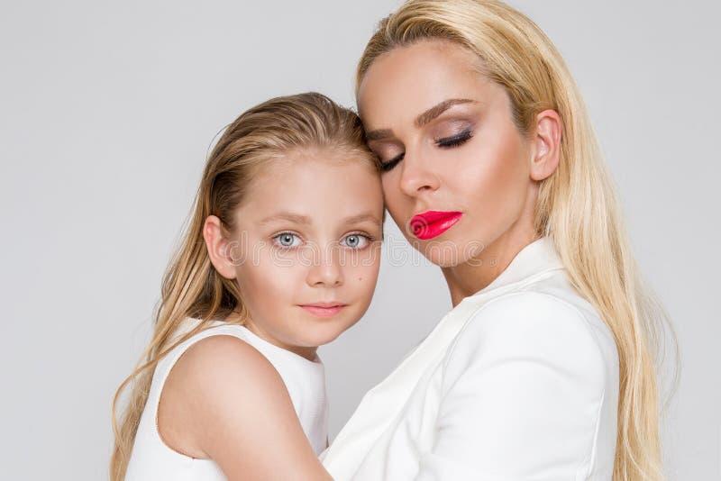充满一起偎依的女儿和展示爱的美丽的妇女母亲,聪明地穿戴在一件白色礼服 免版税库存照片