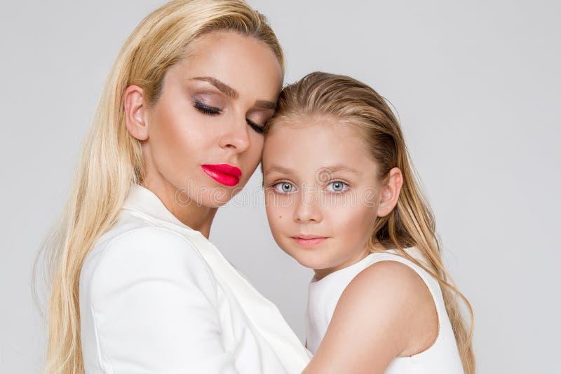 充满一起偎依的女儿和展示爱的美丽的妇女母亲,聪明地穿戴在一件白色礼服 免版税库存图片