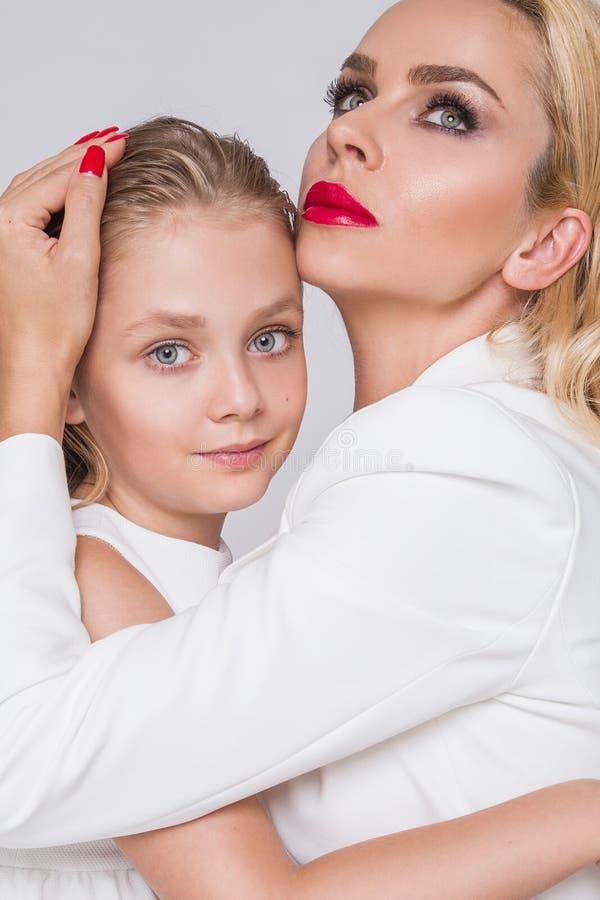 充满一起偎依的女儿和展示爱的美丽的妇女母亲,聪明地穿戴在一件白色礼服 库存照片