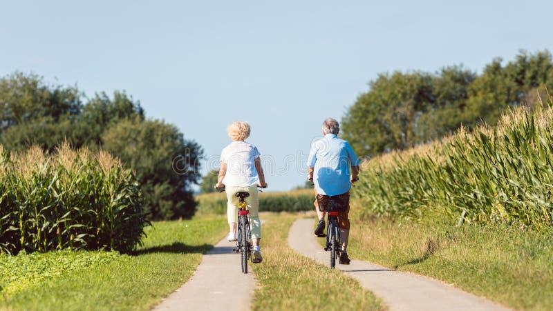 充满信心地今后看资深的夫妇,当乘坐骑自行车时 库存照片