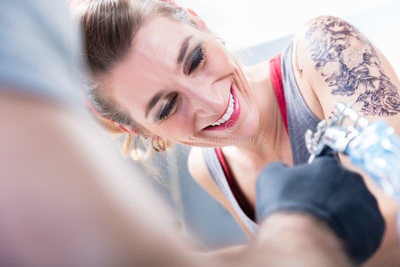 充满信心地微笑在一个现代纹身花刺演播室的快乐的妇女 免版税库存图片