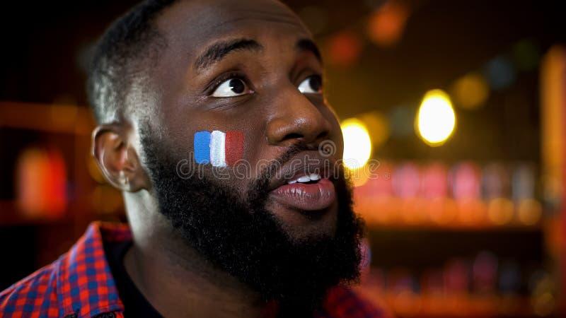 充满希望的情感黑人在眼睛和法国旗子在面颊观看的比赛 免版税库存图片