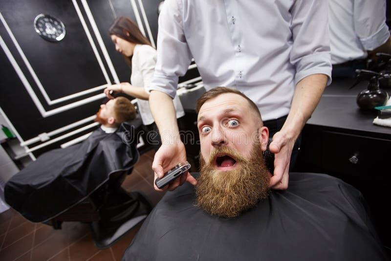 充满恐惧的有胡子的人在理发店坐 免版税库存图片
