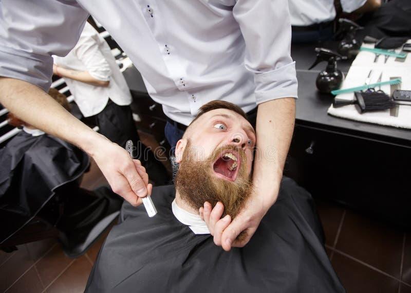 充满恐惧的有胡子的人在理发店坐 库存图片